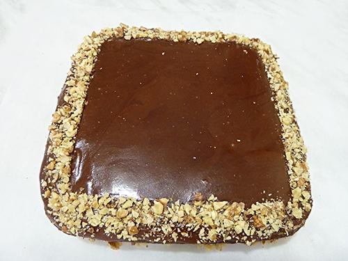 Украшение торта шоколадной глазурью и орехами
